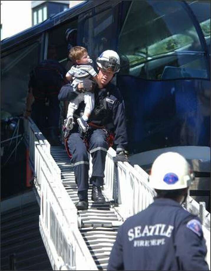 A Seattle firefighter gives a youngster a free ride down the ladder after the Monorail lost power and was stranded between Wall and Battery streets yesterday. After 45 minutes high above Fifth Avenue, 26 people were rescued. Photo: Jeff Larsen/Seattle Post-Intelligencer