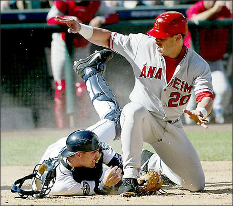 Angels' Brad Fullmer scores on David Eckstein's sacrifice fly as catcher Dan Wilson slides on the ground during the third inning. The throw to the plate bounced off Eckstein's bat on the ground, then off Wilson's glove and flew to the backstop. Photo: / Associated Press