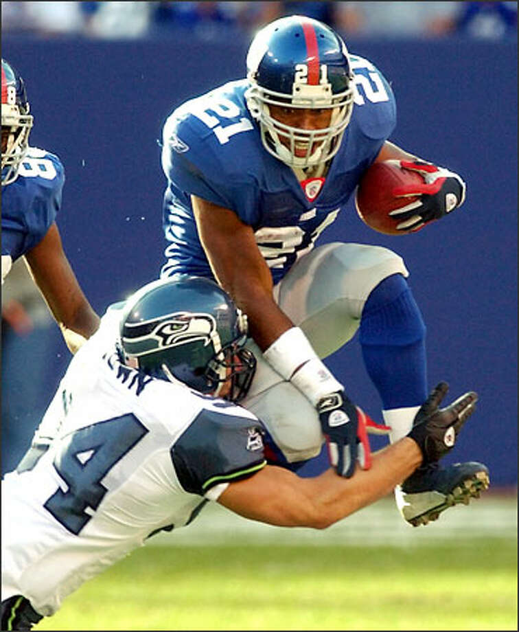 New York Giants running back Tiki Barber is tackled as he attempts to leap over Seahawks outside linebacker Chad Brown in the first quarter. Photo: / Associated Press