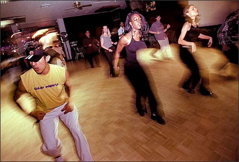 Instructors, from left, Marcelo Garces, Coco Sanders and Rachel Wilson of the Salsa Salvaje Dance Group show off some fast foot work at the China Harbor restaurant. Photo: Loren Callahan/Seattle Post-Intelligencer