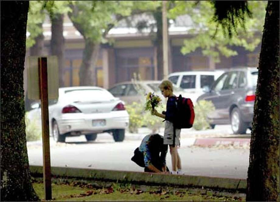 Carol Powers ties her son Brian's shoes before walking him to school yesterday morning for his belated first day of class after teachers voted to accept the school district offer. Brian was bringing flowers for his third-grade teacher at Issaquah Valley Elementary School. Photo: Grant M. Haller/Seattle Post-Intelligencer