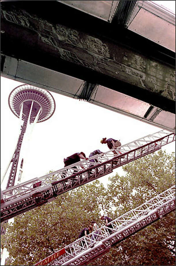Firefighters help Emi Horiaawa of Nagano, Japan, on the upper ladder, and Mary Perez of San Francisco down off the stalled Monorail yesterday. Photo: Loren Callahan/Seattle Post-Intelligencer