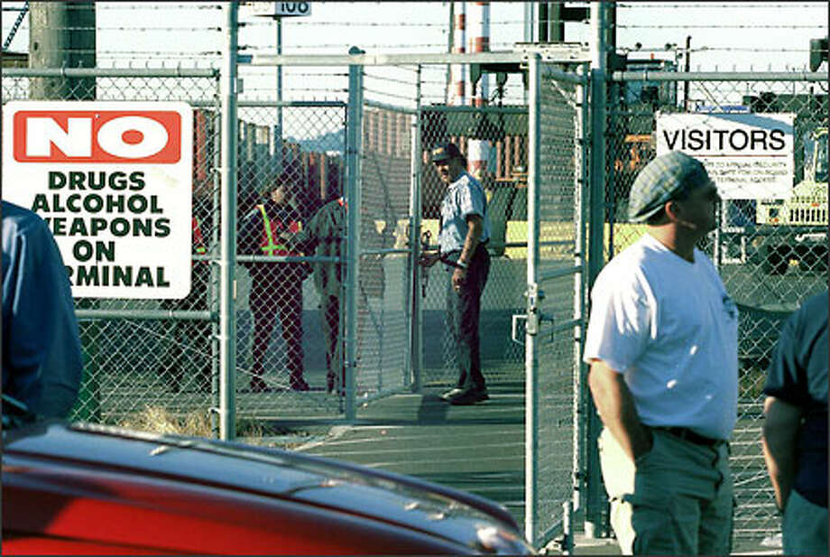 Security personnel chain the gates at the Port of Seattle's Terminal 5 after the Pacific Maritime Association shut down all West Coast ports yesterday in a labor dispute. Photo: Loren Callahan/Seattle Post-Intelligencer