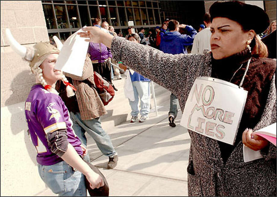 A Vikings fan passes as Marguerite Richard hands out fliers during yesterday's protest at Seahawks Stadium. Photo: Jeff Larsen/Seattle Post-Intelligencer