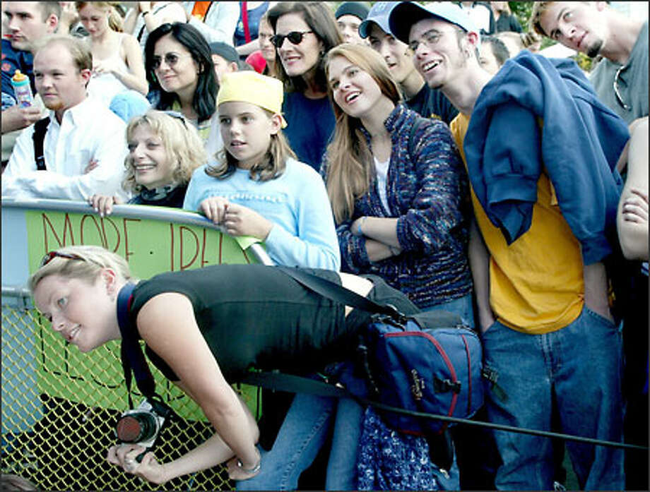 Leanne Grimsey, 25, leans over a fence for a better view to take a picture of Dave Matthews, who played at a free benefit concert. Photo: Renee C. Byer/Seattle Post-Intelligencer