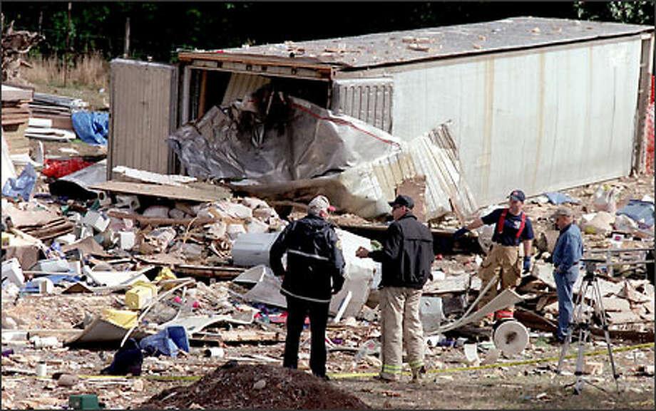 Auburn police and fire authorities investigate the site yesterday of an explosion in Auburn that critically injured Sharon Massena, 61. Photo: Scott Eklund/Seattle Post-Intelligencer