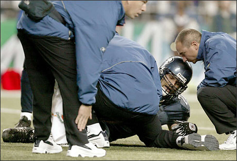 A Seahawks trainer signals that Steve Hutchinson has an injury to his ankle. The left guard had surgery yesterday and will be out for at least eight weeks. Photo: Grant M. Haller/Seattle Post-Intelligencer