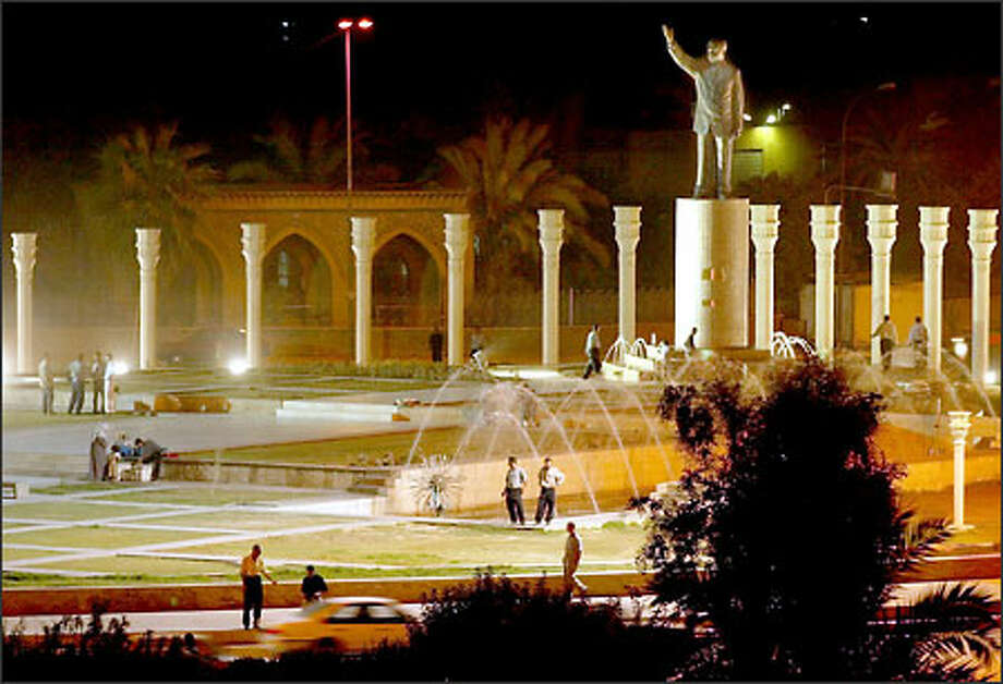 A statue of Saddam Hussein looks down as Iraqis stroll in Baghdad's Abatash Ramadan Square. Photo: Paul Kitagaki Jr./Seattle Post-Intelligencer