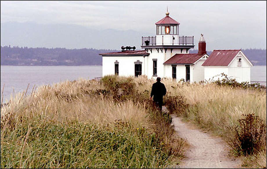 Joe Navone of Seattle walks the trail to the West Point lighthouse near Discovery Park, to be given away by the U.S. Department of the Interior. Photo: Loren Callahan/Seattle Post-Intelligencer
