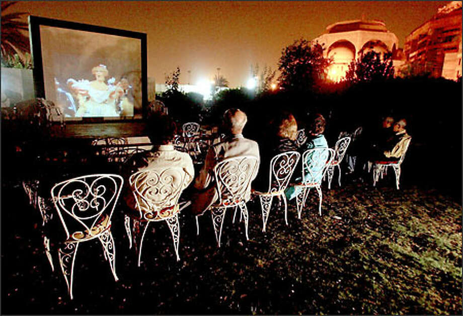 "Iraqis watch a CD movie of the opera ""The Tales of Hoffman,"" which was playing on an outdoor screen at the Orfali Art Gallery in Baghdad. Photo: Paul Kitagaki Jr./Seattle Post-Intelligencer"