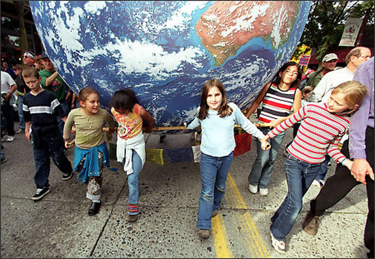 Children carry a giant globe as they walk along Broadway Avenue in Capital Hill yesterday. The march went from Volunteer Park to Westlake Center and drew an estimated 6,000 to 8,000 people.