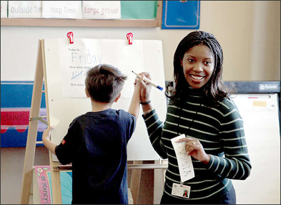 Preschool teacher Felecia Wells helps Huy Phi, 4, spell a word at the touchy-feely The New School at South Shore. Photo: Meryl Schenker/Seattle Post-Intelligencer