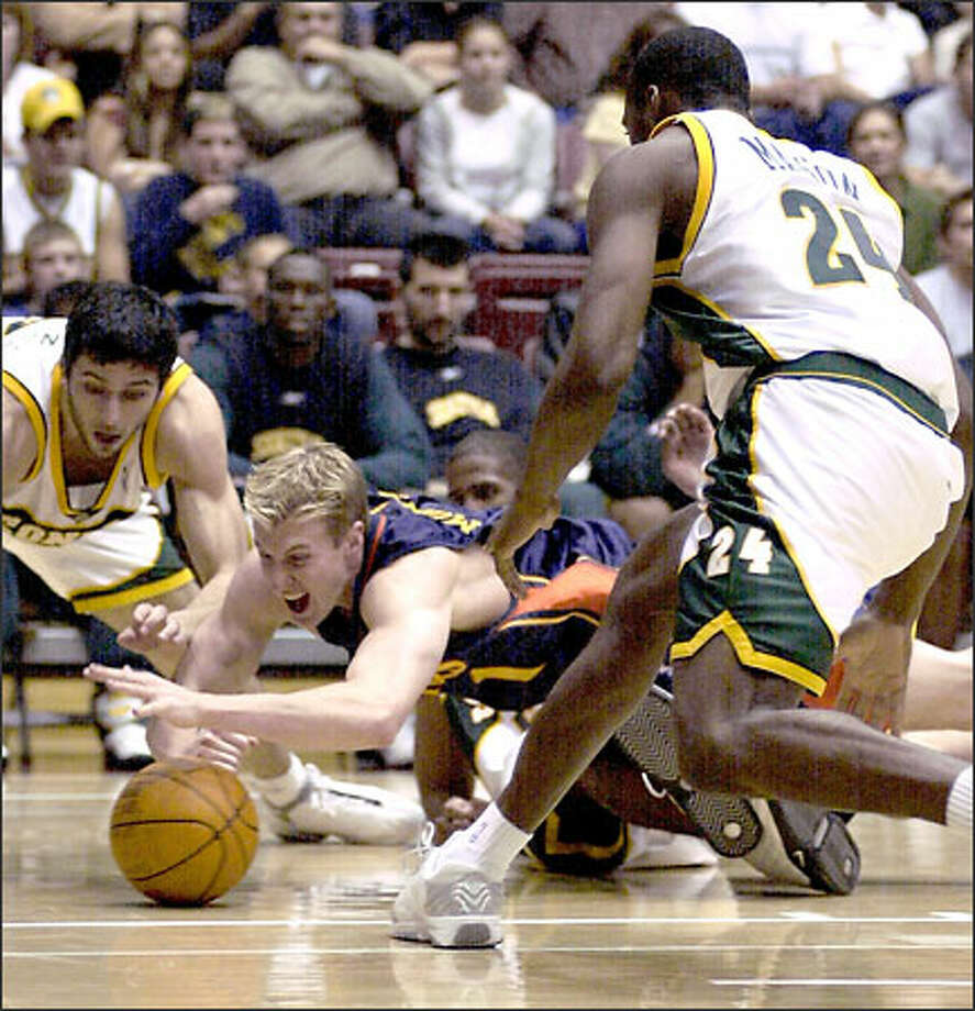 Golden State forward Troy Murphy dives for a loose ball in between two Sonics, Vladimir Radmanovic and Desmond Mason. Photo: / Associated Press