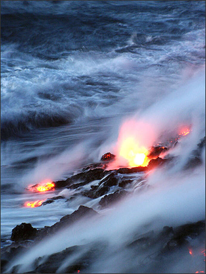 Lava drops over the cliffs and enters the ocean along a half-mile stretch of coastline in Hawaii Volcanoes National Park. Photo: David Jordan/Special To The Post-Intelligencer