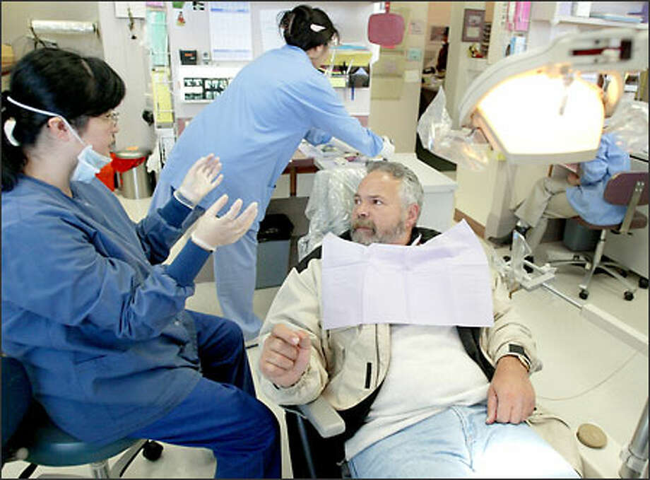 Greg Wick discusses options for a full top denture with Dr. Anna Lee, left. After being sober for three years, Wick decided he wanted to fix his teeth. He has been going to the Georgetown Dental Clinic for seven months. Photo: Meryl Schenker/Seattle Post-Intelligencer