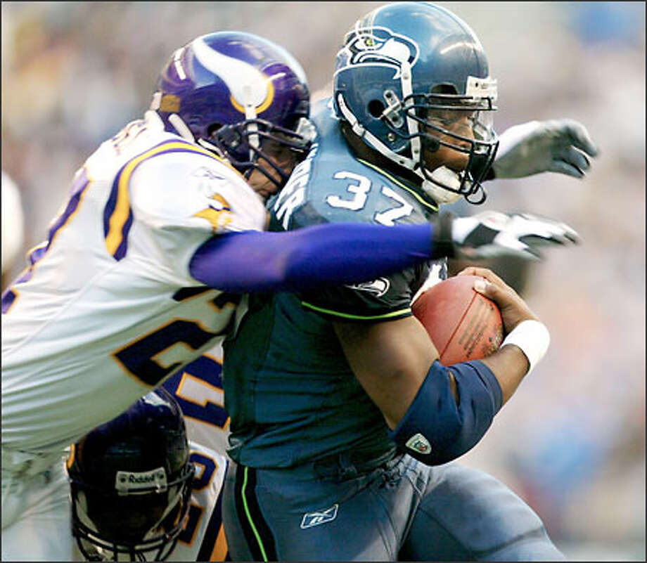 Shaun Alexander, hit by Minnesota's Brian Russell in their game Sept. 29, scored five touchdowns against the Vikings. Photo: / Associated Press