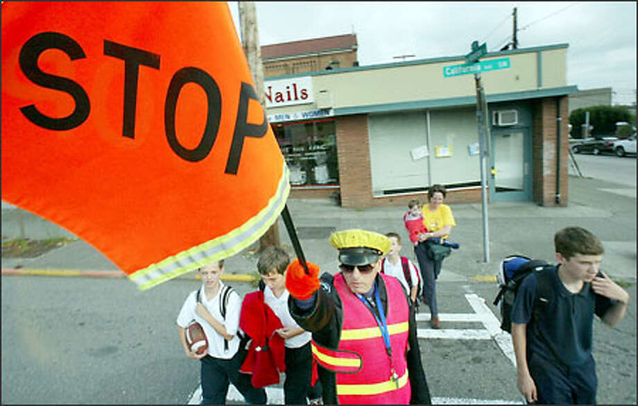 Crossing guard David McGinnis stops traffic as students and others cross California Avenue Southwest at Southwest Genesee Street in West Seattle. Photo: Dan DeLong/Seattle Post-Intelligencer