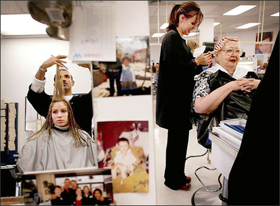 Francisco Renteria (reflected in a mirror), a student at the Bellevue Beauty School, cuts the hair of Remi Spector, 16, as student Corrie Ebel styles Maxine Kerfoot. Photo: Dan DeLong/Seattle Post-Intelligencer