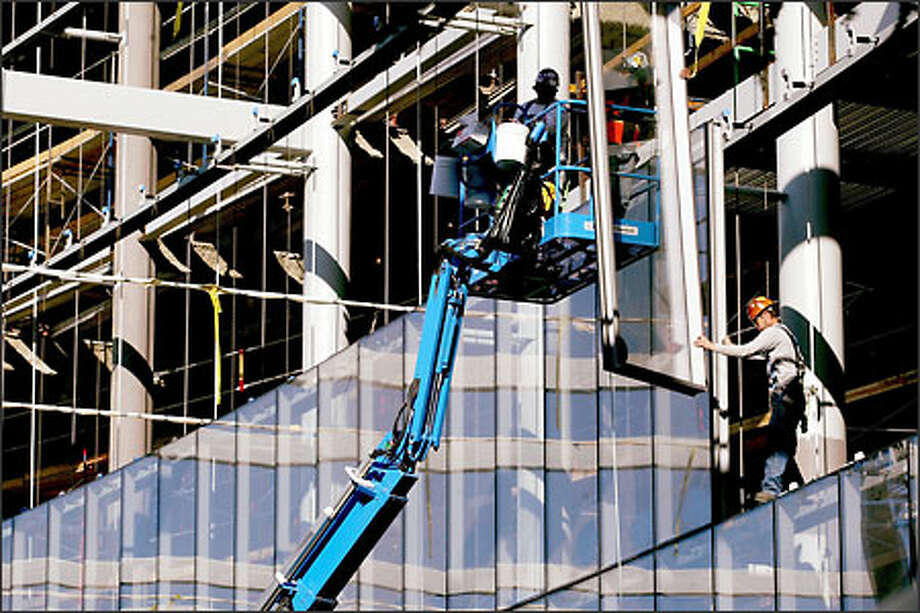 Workers install a huge wall of windows at Marion Oliver McCaw Hall, the new opera house at Seattle Center. Photo: Dan DeLong/Seattle Post-Intelligencer