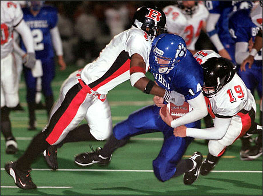 Bothell's Sean Gallacher gets sandwiched on a tackle by Ballard's Matt McGiboney (19) and Keaunta Bankhead at Bothell's Pop Keeney Stadium. Photo: Loren Callahan/Seattle Post-Intelligencer