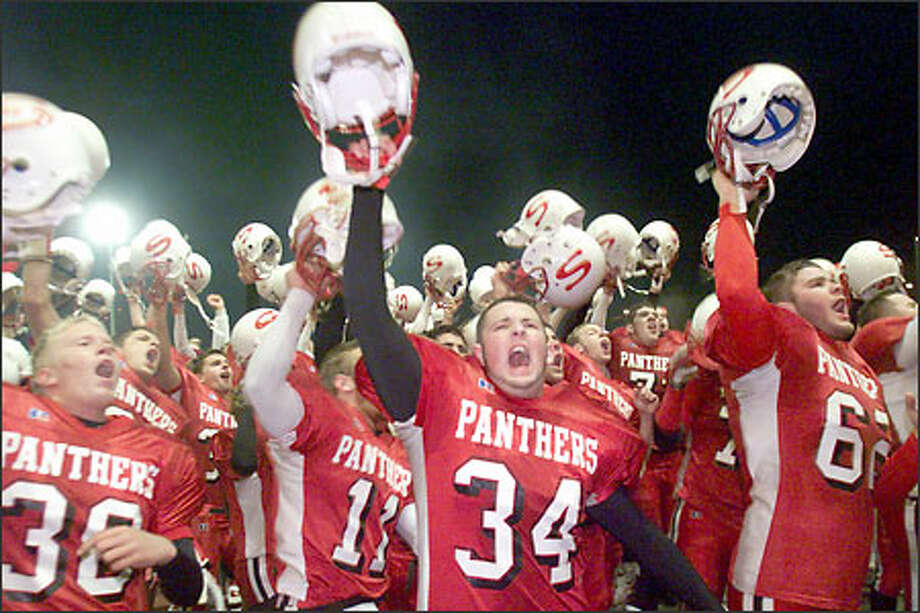Snohomish players, led by senior linebacker Cody Brown (34), celebrate after repelling Oak Harbor's late scoring threat for a 14-12 victory that left them atop the Wesco North Division. Photo: Scott Eklund/Seattle Post-Intelligencer