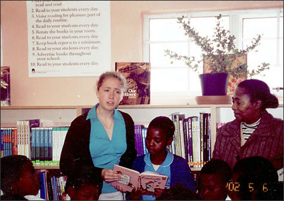 """Marta Nimlos shares a book with students in a South African school where she was bestowed with an African name, """"Lelethu,"""" meaning """"our pride, our joy, our everything."""" Photo: /"""