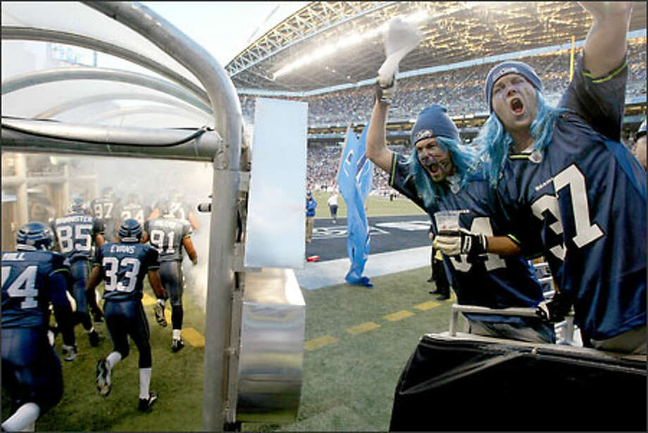 """Seahawks fans Jeremy Janssen, left, and Steve Monger, both from Port Angeles, cheer as the home team takes the field at the first """"Monday Night Football"""" game in Seattle in 10 years. Photo: Dan DeLong/Seattle Post-Intelligencer"""