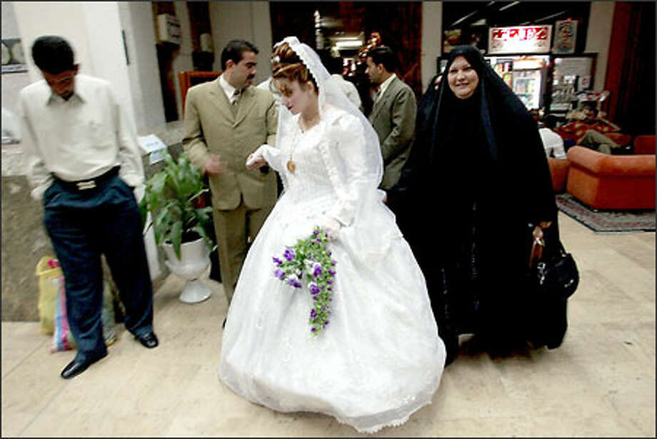 Newlywed couples retire to their rooms after having their photos taken in the lobby of Baghdad's Palestine Hotel. Wedding parties remain a common sight, usually on Thursdays, the day before the Muslim holy day. Photo: Paul Kitagaki Jr./Seattle Post-Intelligencer