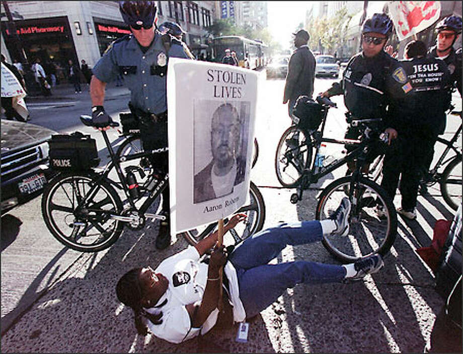 A demonstrator is pushed down in front of Seattle police officers yesterday during a march protesting the decision not to charge Deputy Mel Miller in the killing of Robert Lee Thomas Sr. (Editor's Note: This caption has been changed since original publication to indicate the demonstrator was pushed down and did not fall of his own volition.) Photo: Paul Joseph Brown/Seattle Post-Intelligencer