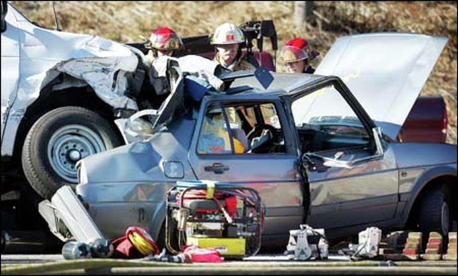 Firefighters look over the wreckage of a fatal car accident yesterday on northbound Interstate 5 near Northeast 145th Street. The accident backed up traffic for miles. Photo: DAN DELONG/P-I