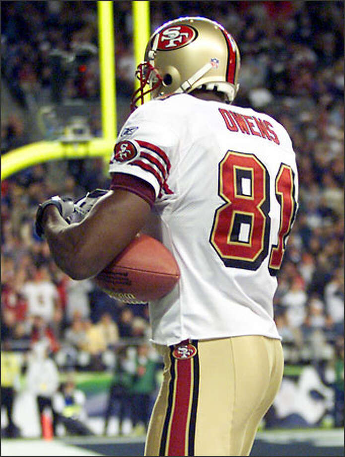 The 49ers' Terrell Owens, autographing the football he caught for the game-winning touchdown against the Seahawks on Monday, was not berated by his coach for the move. Photo: / Associated Press