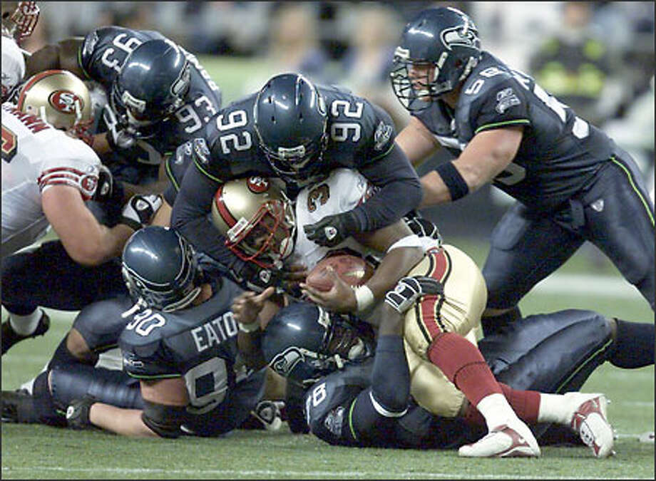 San Francisco's Kevin Barlow gets stuffed by Antonio Cochran (78), bottom, Lamar King (92) and a host of other Seahawks defenders on a fourth-quarter run in Monday's 28-21 49ers victory. The defense has just three days to prepare for Sunday's game at St. Louis. Photo: SCOTT EKLUND/P-I