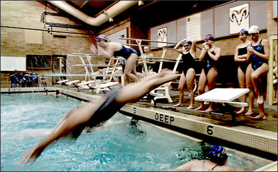 The Mount Rainier High School girls swim team practices their starts. They share the pool with Tyee High School, which was using the other end of the pool. Photo: Scott Eklund/Seattle Post-Intelligencer