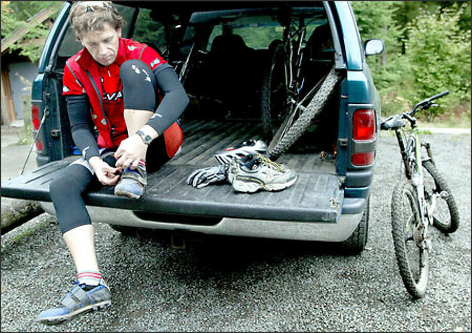 Kevin Myette, director of quality assurance at REI, straps his biking shoes on before testing a Ponderosa FSL mountain bike on the trails at Tiger Mountain. Photo: Renee C. Byer/Seattle Post-Intelligencer