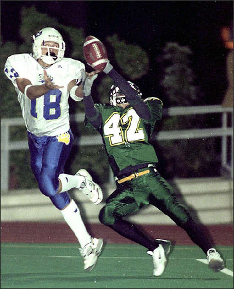 Kentridge High School's Brandon Bentrott (42) defends against Tahoma receiver Austin Proctor last night in a battle of unbeaten teams at French Field in Kent. Photo: Loren Callahan/Seattle Post-Intelligencer