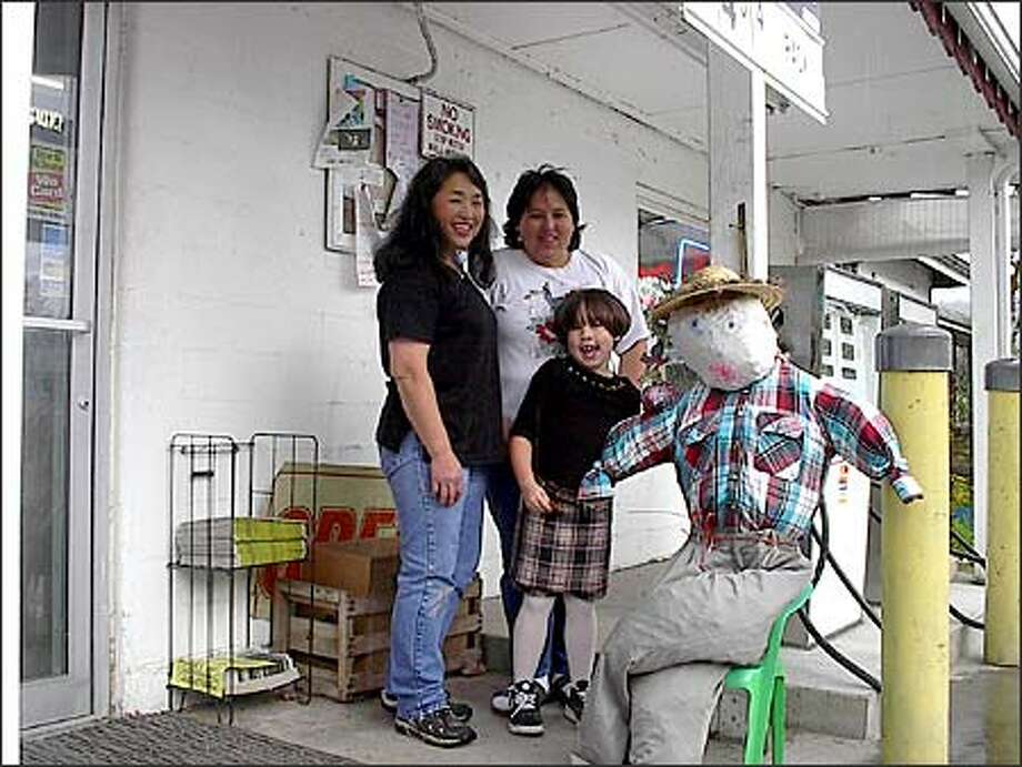 "Yumi Jujo (left), her daughter Erickia Coger (white shirt) and granddaughter Denise Coger in front of the Yummy Store, along with a Halloween ""scarecrow"" figure made by Yumi and Denise. Photo: /"