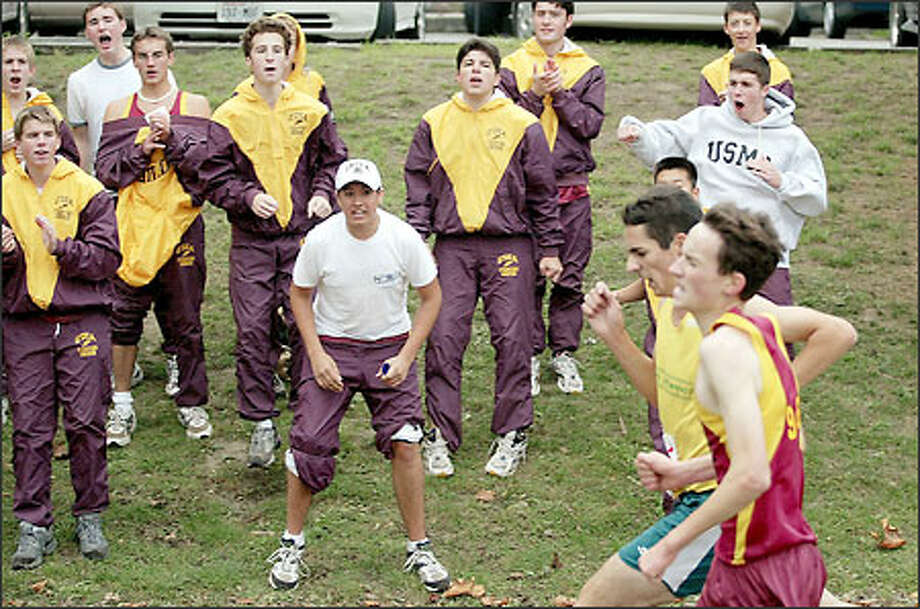 The O'Dea junior varsity team cheers on varsity runner Mike Kilburg, right, as he nears the finish line neck-and-neck with eventual winner Brendan Swenson of Blanchet. Photo: Mike Urban/Seattle Post-Intelligencer