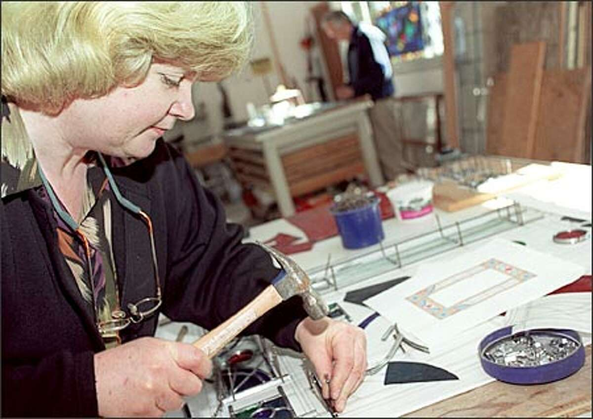 Judi Frankel pounds a nail used as a guide to create the framing for a stained-glass window in her Seattle home studio, known as Annapurna Glass, with her husband, Ed Brown, in background.