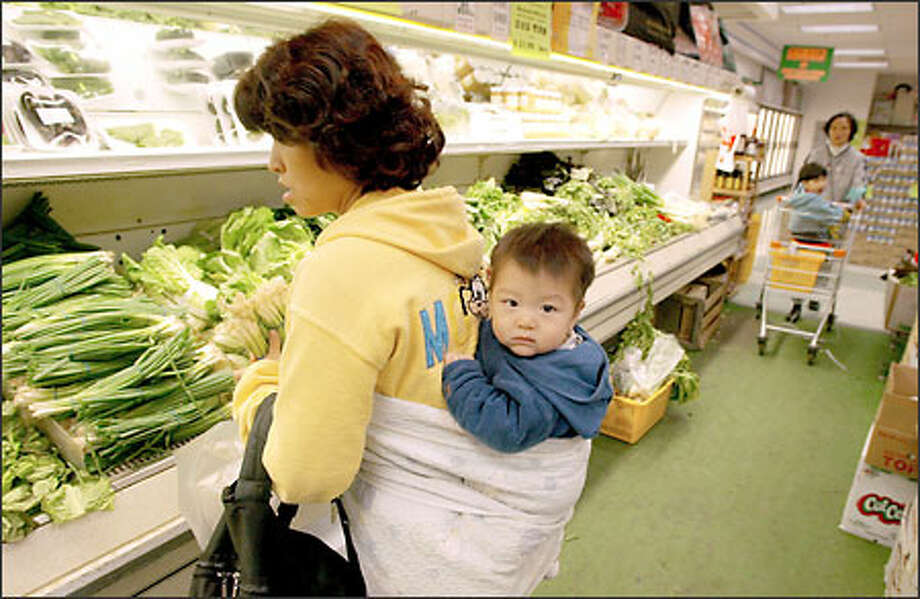With 6-month-old son Brian Ji Woong Hwang riding in a backpack called a podaegi, Korea-born Ji Soon Hwang shops at Pal-Do World grocery in Federal Way. Photo: Gilbert W. Arias/Seattle Post-Intelligencer