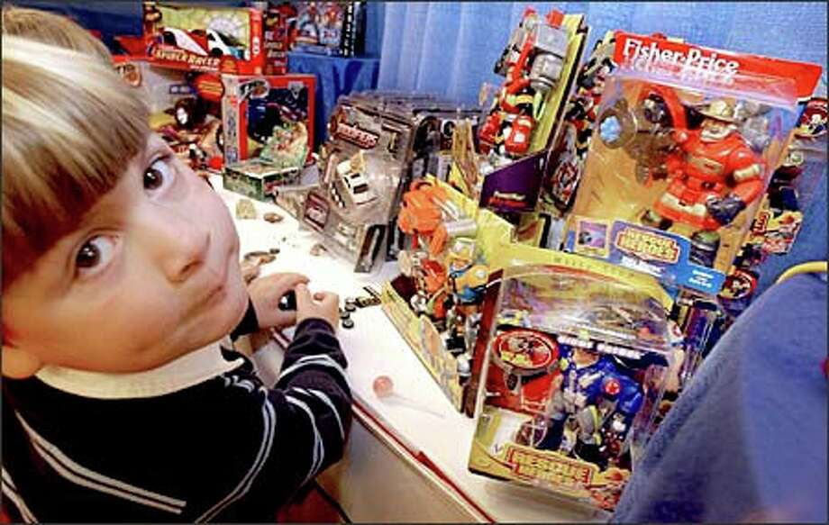 Hutch Tyree, 4, of New York City checks out the assortment of Fisher Price Rescue Heroes at the PlayDate Toy Fair trade show in New York last week. Photo: / Associated Press