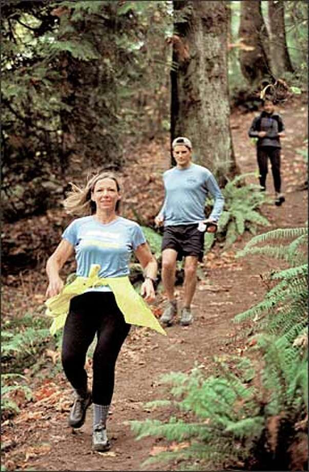 In St. Edward State Park, trail runner Cheri Gillis of Woodinville is followed by Charlie Crissman of Seattle and Lorraine Arnold of Woodinville. Photo: Loren Callahan/Seattle Post-Intelligencer