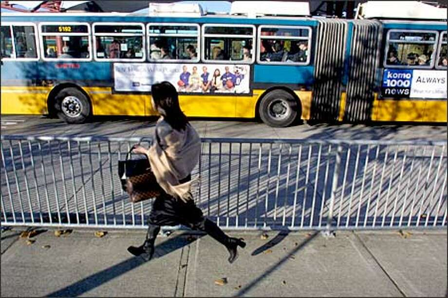 A passenger runs to catch her bus at the Northgate Transit Center. The Northgate park and ride is among the most used, often filled to capacity. Photo: Phil H. Webber/Seattle Post-Intelligencer