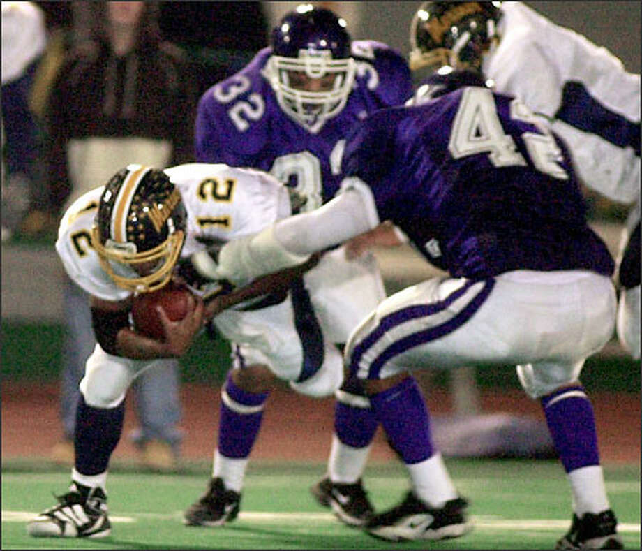 Kamiak's Levon Rector (32) and Joe Huss pile on Mariner quarterback Moa Palepale. Kamiak clinched a state playoff berth. Photo: Ron Wurzer/P-I