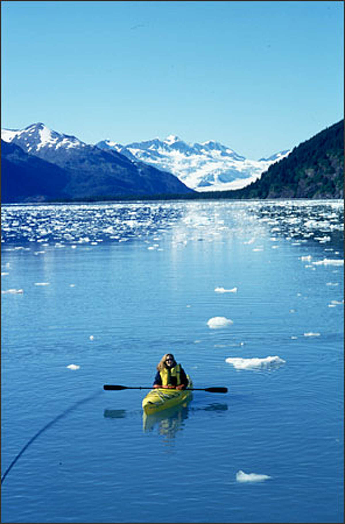 Bellamy Pailthorp, of KNKX Radio, kayaks in Alaska's Harriman Fjord, as part of boat trip in Prince William Sound. .