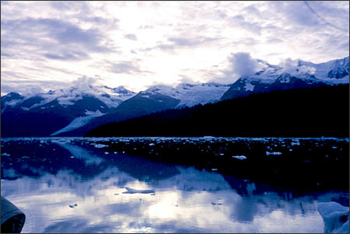 Ten-thousand-foot peaks are reflected in the ice-dappled waters of College Fjord, one of approximately 40 fjords on Prince William Sound.