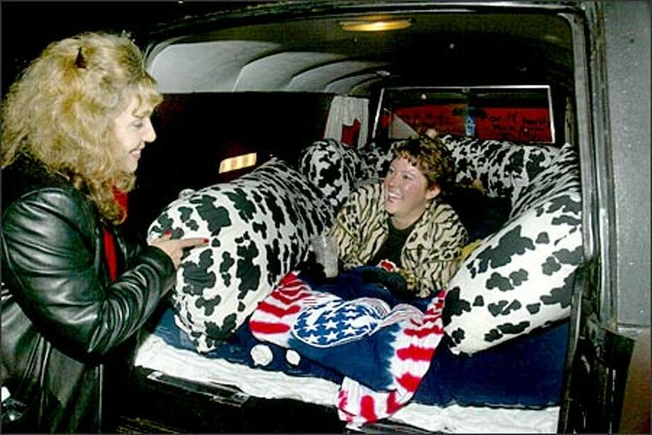 Rolling Stones fan Belinda Mastrangelo talks with Mary LaFleur, in her 1979 Cadillac hearse, in Tacoma last night. LaFleur was hoping the Stones would autograph the hearse. Photo: Grant M. Haller/Seattle Post-Intelligencer