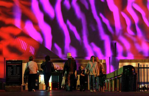 People pass the Institute of Texan Cultures in HemisFair Park during Luminaria 2011 on Saturday, March 12, 2011. Photo: Edward A. Ornelas/Express-News / SAN ANTONIO EXPRESS-NEWS NFS