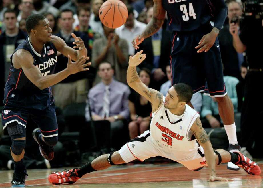 Connecticut's Kemba Walker (15) and Louisville's Peyton Siva (3) fight for control of the ball during the first half of an NCAA college basketball game at the Big East Championship, Saturday, March 12, 2011, in New York. (AP Photo/Frank Franklin II) Photo: AP