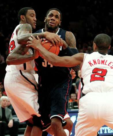 Connecticut's Alex Oriakhi (34) drives past Louisville's Terrence Jennings (23) and teammate Preston Knowles (2) during the first half of an NCAA college basketball game at the Big East Championship Saturday, March 12, 2011, in New York. (AP Photo/Frank Franklin II) Photo: AP