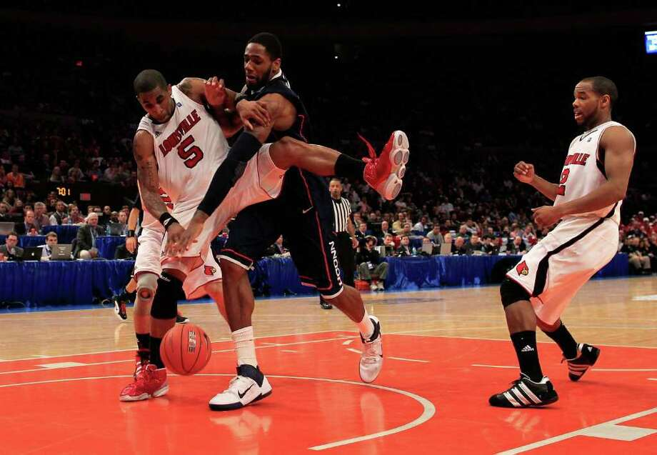 NEW YORK, NY - MARCH 12: Chris Smith #5 of the Louisville Cardinals and Alex Oriakhi #34 of the Connecticut Huskies battle for a loose ball during the championship of the 2011 Big East Men's Basketball Tournament presented by American Eagle Outfitters at Madison Square Garden on March 12, 2011 in New York City.  (Photo by Chris Trotman/Getty Images) *** Local Caption *** Chris Smith;Alex Oriakhi Photo: Chris Trotman, Getty Images / 2011 Getty Images